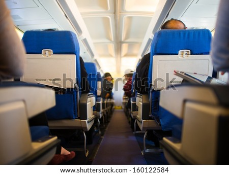 Passengers inside the cabin of a commercial airliner during flight - stock photo