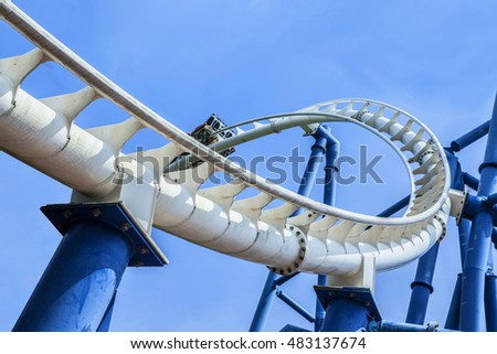 passengers restrained in seats of steel roller coaster trains climbing to a higher position in white rail tracks with blue steel supporting posts against blue sky