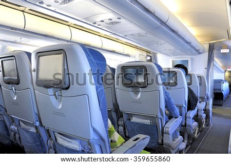 Passengers sitting in tourist class seats inside an airplane