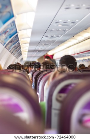 Passengers sitting on their chairs in airplane cabin - stock photo