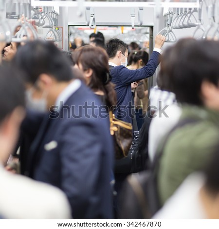 Passengers traveling by Tokyo metro. Business people commuting to work by public transport in rush hour. Shallow depth of field photo. Square composition. - stock photo
