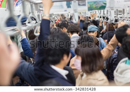 Passengers traveling by Tokyo metro. Business people commuting to work by public transport in rush hour. Shallow depth of field photo. Horizontal composition. - stock photo