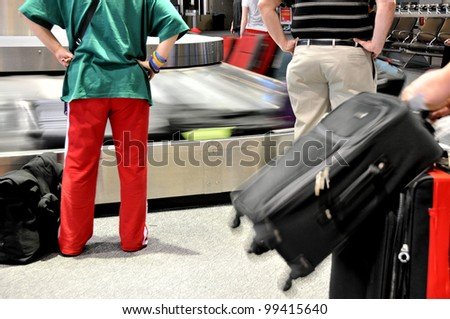 Passengers wait for baggage at airport carousel - stock photo