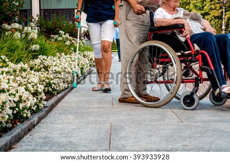 Passing by people in the park and an elderly couple in a wheelchair - stock photo