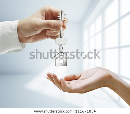 passing key against backdrop of white room