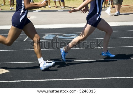 Passing the baton during relay competition - stock photo