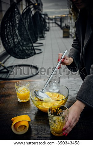 Passion fruit and orange punch, girl pouring into glass