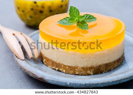 Passion fruit cheesecake with fresh mint leaves on dark background. Passion fruit cheesecake setup with Passion fruit juice. Selective focus depth of field.