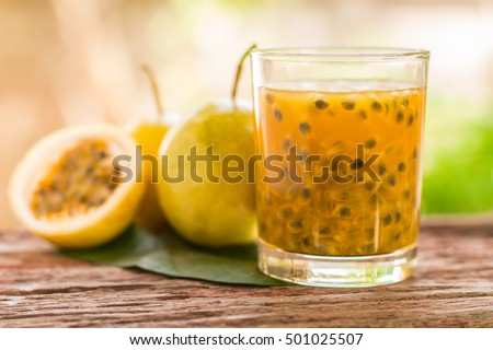 Passion fruit - Passion fruits half and juice with leaves on the vintage wooden background. Closeup, Select focus.