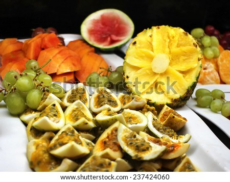 Passion fruit pieces and other tropical fruits - stock photo