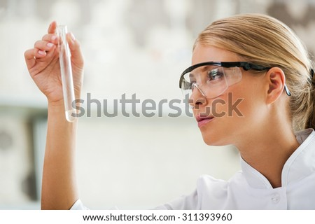 Passionate about her work. Side view of young female scientist holding test tube and looking at it while working in the laboratory - stock photo