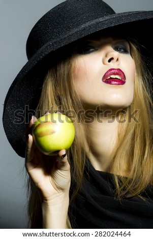 Passionate blonde girl in retro black hat with bright make up looking away holding fresh green apple standing on gray background copyspace, horizontal picture - stock photo