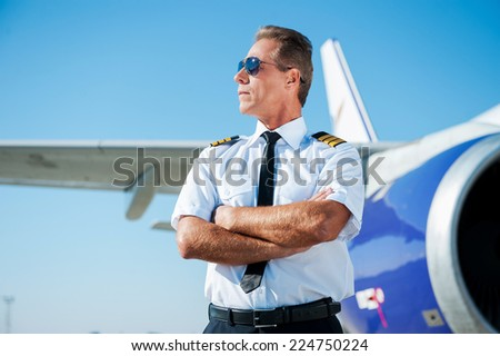 Passionate by sky. Confident male pilot in uniform keeping arms crossed and looking away with airplane in the background