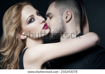 Passionate couple. Beautiful young man and blond woman closeup. Woman hugging man. Love. Flirt. Kiss. Lovers. Valentine couple - stock photo