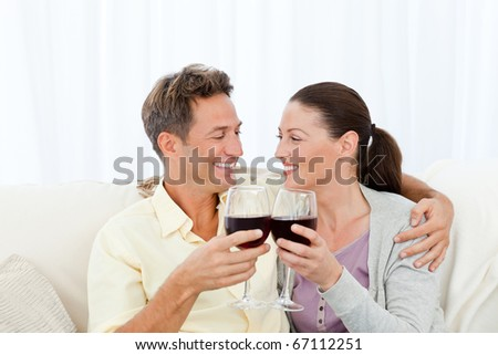 Passionate couple drinking red wine while relaxing on the sofa - stock photo