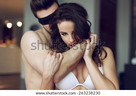 Passionate couple foreplay in luxury flat, sexy woman in bra bite man arm, young lover with lace eye cover - stock photo