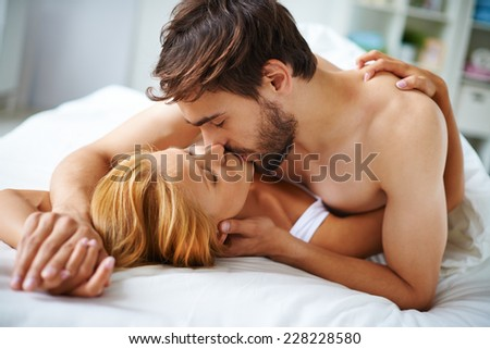 Passionate couple lying on bed and kissing - stock photo