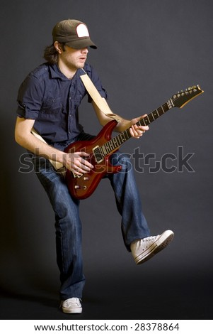 passionate guitarist playing his electric guitar with one leg in the air