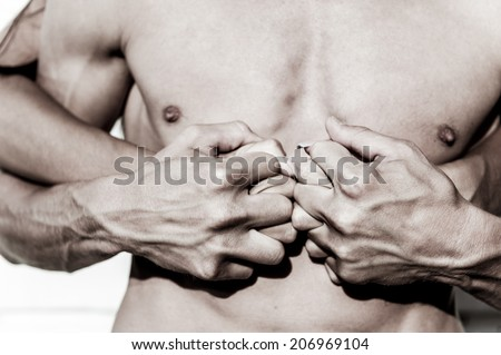 Passionate hug, male torso and female hands. - stock photo