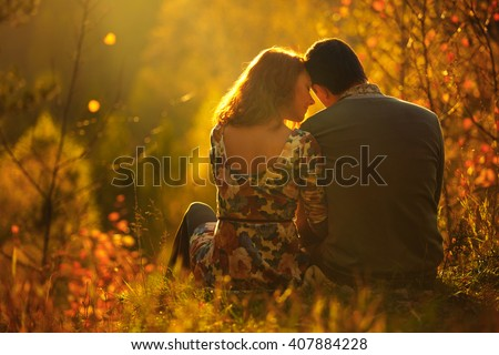 passionate love in the autumn park. A young couple. Sitting in a winter fairy and the magical forest. - stock photo