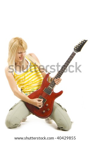 passionate rock girl playing an electric guitar on her knees