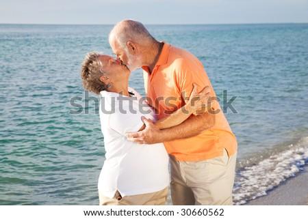 Passionate senior couple kissing on the beach. - stock photo