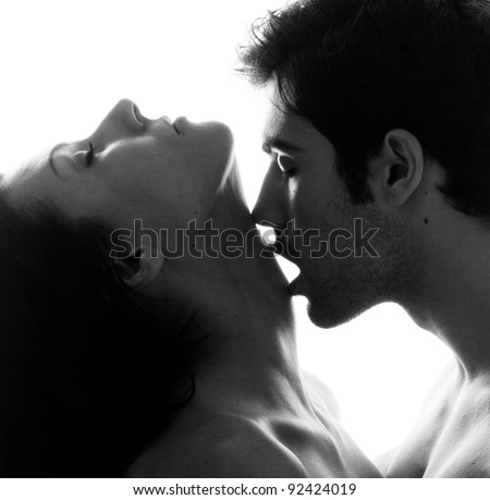 Passionate sensual attractive young couple in love, man caresses woman neck, isolated black and white portrait - stock photo