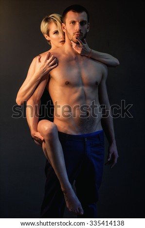 Passionate sexual fitness couple posing semi naked on dark background - stock photo