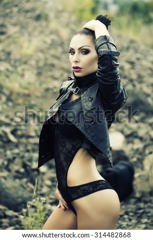 Passionate sexy brunette young wild woman with bright make-up ponytail and beautiful bottom in black leather biker jacket and erotic lace lingerie outdoor on natural background, vertical picture - stock photo