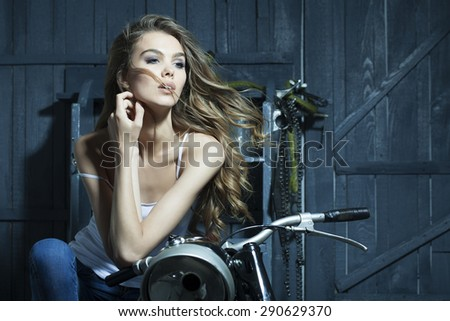 Passionate sweet young girl in white vest sitting on old fashioned motorcycle in garage on grey wooden wall background copyspace, horizontal picture - stock photo