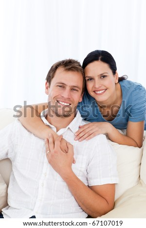 Passionate woman hugging her boyfriend while relaxing on the sofa at home - stock photo