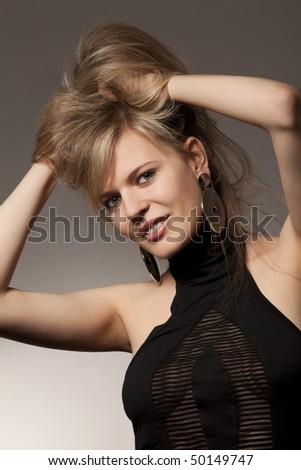 Passionate woman in evening dress fluffing up dark hair, both hands risen behind head