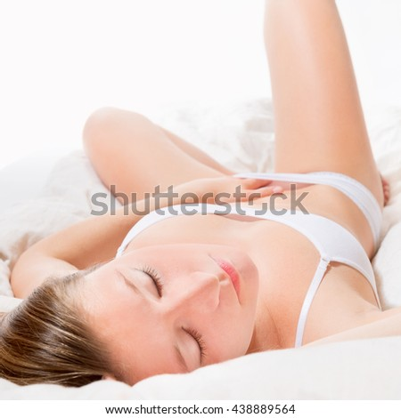 Passionate woman wearing white underwear lying on white bed with closed eyes