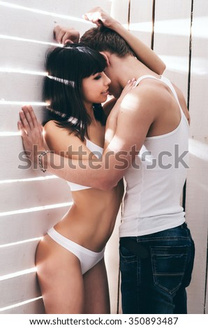 Passionate young couple hugging near a wall. Woman in underwear.