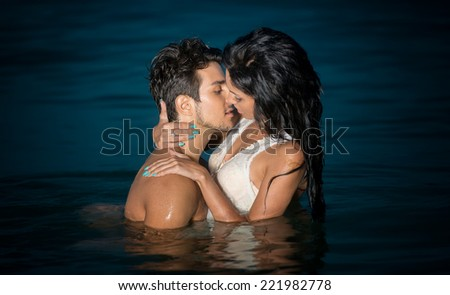 Passionate young couple in water - stock photo
