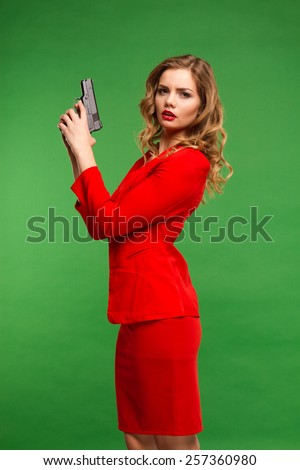 passionate young woman in red dress standing on a green background with a gun. lifestyle - stock photo