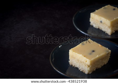 Passionfruit Slice on Plates on Angle Dark Background with Copy Space