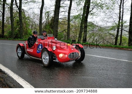 PASSO DEL CERRETO, ITALY - APRIL 27: A red Fiat Gilco 1100 Sport takes part to the GP Terre di Canossa classic car race on April 27, 2014 near Passo del Cerreto. The car was built in 1948. - stock photo
