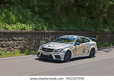 PASSO DELLA FUTA (FI), ITALY - MAY 21: driver and co-driver on a racing car Mercedes-Benz C63 AMG (2012) in historical italian rally Mille Miglia on May 21, 2016 in Passo della Futa (FI) Italy