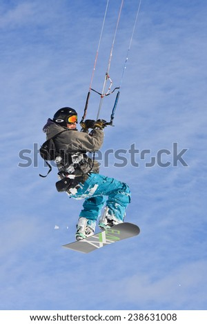 PASSO GIAU, ITALY - MARCH 11, 2012 - Snowkiter jumping with a snowboard in Passo Giau, Italy on a sunny winter day. - stock photo