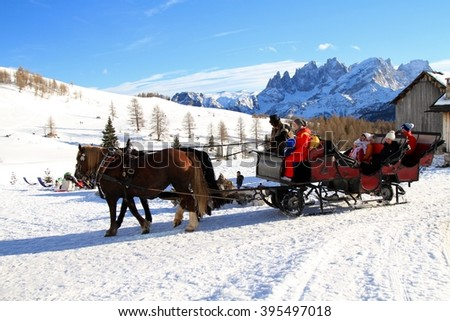 PASSO SAN PELLEGRINO,ITALY, FEBRUARY 21, 2016: tourists on a sleigh carriage pulled by two horses on Trentino Dolomites, Fuciade, Passo San Pellegrino. - stock photo