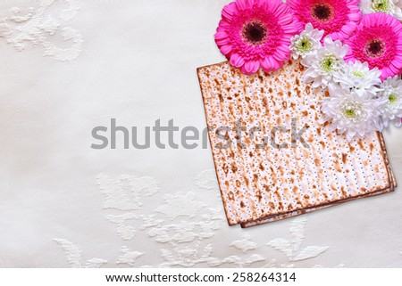 passover background. matzoh (jewish passover bread) and flowers on white table cloth - stock photo