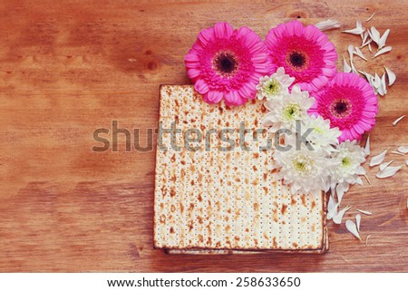 passover background. matzoh (jewish passover bread) and flowers on wooden table - stock photo
