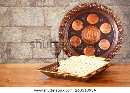 passover background. wine and matzoh (jewish passover bread) on wooden table and wall texture from jerusalem stone  - stock photo