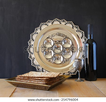 Passover background. wine and matzoh (jewish passover bread) over wooden black background.  - stock photo
