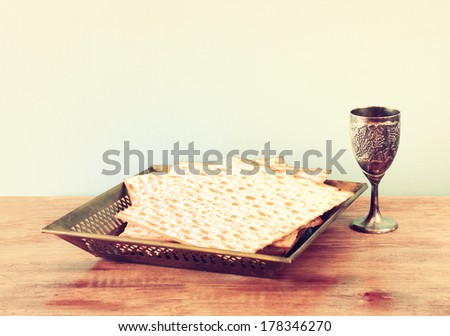 passover background. wine and matzoh over wooden table. vintage effect process.