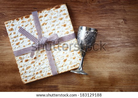passover background. wine cup and matzoh over wooden table.  - stock photo