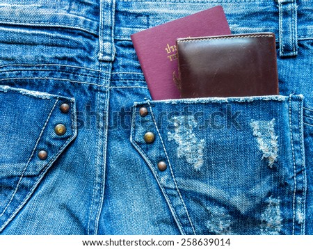 Passport book and wallet in back blue jeans pocket/ traveling concept - stock photo