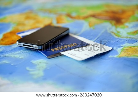 Passport, ticket, phone on a background map of the world. Traveling concept - stock photo