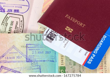 Passport, visa immigration stamps, and boarding pass - stock photo